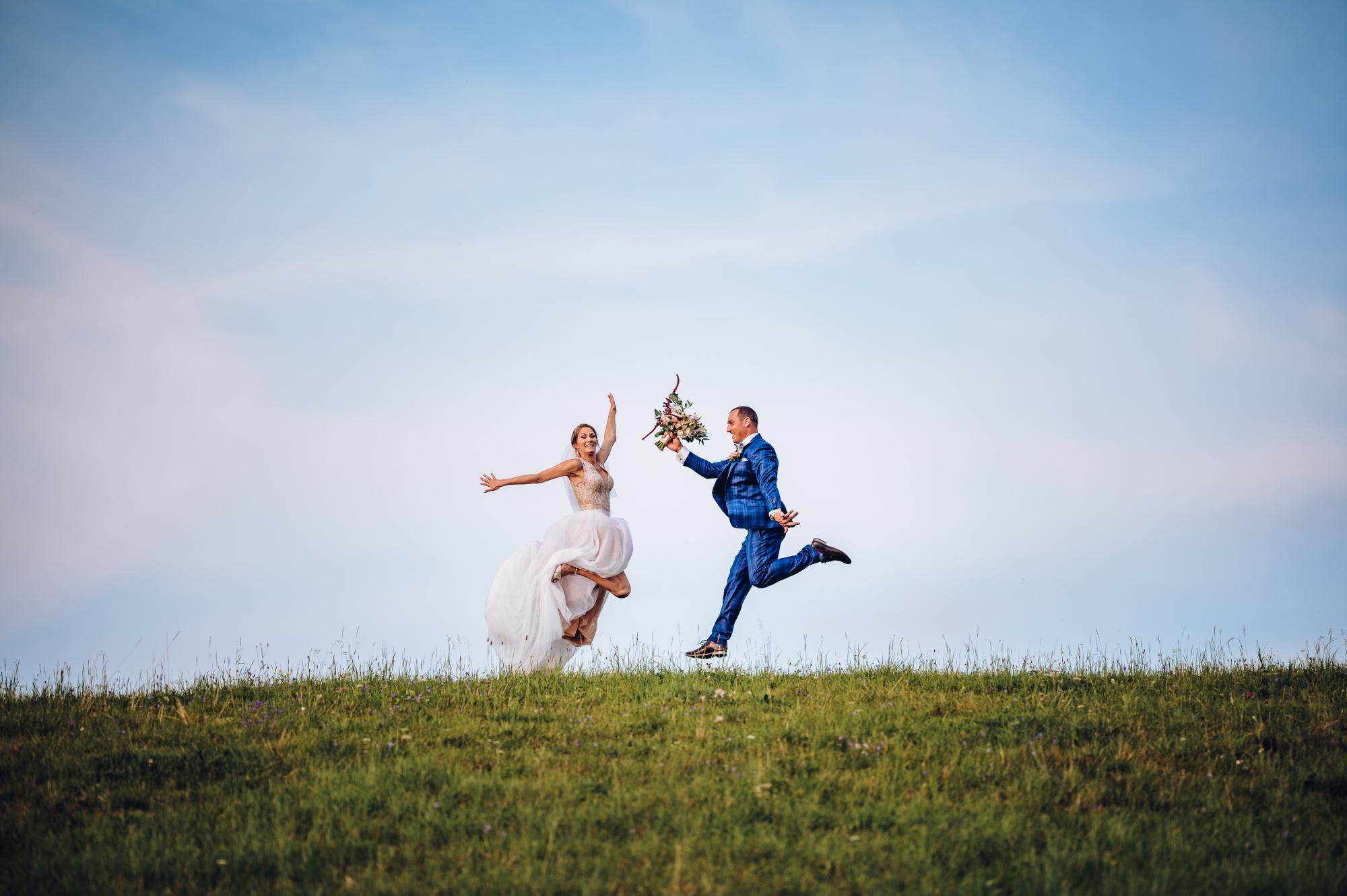 Ženich s nevěstou skáčí na kopci
